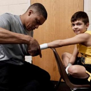 Black man in gray shirt taping up the hand of a young white boy in a yellow tank top