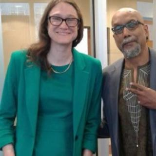 Tall thin white woman smiling with glasses and a green dress next to an older black man in a suit making a peace sign