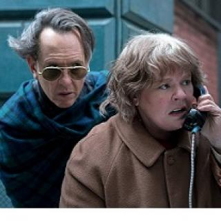 A man with sunglasses and hair blowing in the wind hovering behind a woman looking upset talking into a pay phone