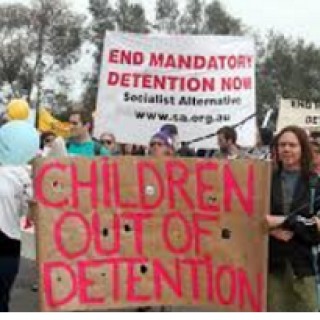 People outside at a rally holding signs saying Children out of detention and End Mandatory Detention Now