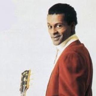 Black man in red suit holding a guitar