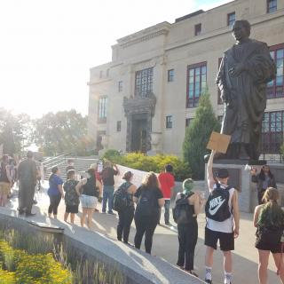 People protesting outside City Hall and large Columbus statue