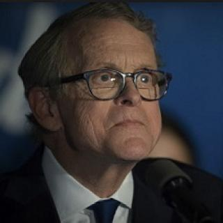 Older white man with glasses looking weird and crazy in a suit at a microphone
