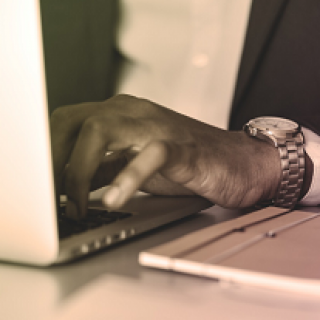 Extreme close up of black man's hand wearing a watch typing on a laptop