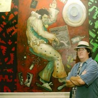 White man in blue shirt with straw hat with arms folded standing in front of huge mural of Elvis Presley
