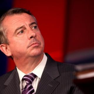 Middle aged white guy with receding brown hair looking sideways with a worried look on his face, wearing a gray suit with a purple and white striped tie