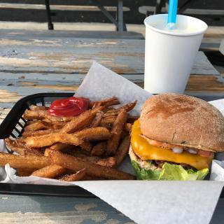 A tray on a wooden table outside with a white cup and blue straw, a bunch of french fries and a burger with visible lettuce and cheese