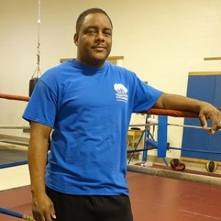 Black man in blue t-shirt standing next to a boxing ring