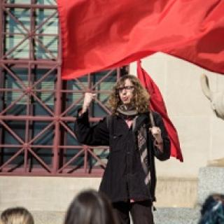 Young white man with long brown curly hair and glasses holding a very large red flag standing in front of a crowd raising his fist in the air