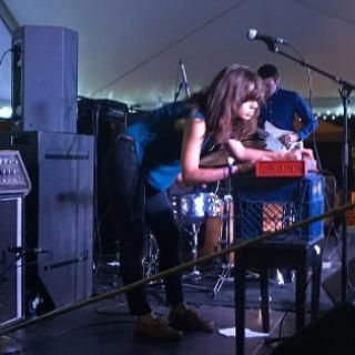 Dark haired woman leaning over a keyboard with a band on a stage