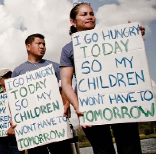Two Latino people holding signs saying I go hungry so my children won't have to tomorrow