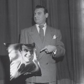 Black and white photo of white man in a suit pointing to a picture of himself in his hand