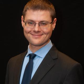 White man in a suit and glasses smiling