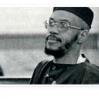 Black and white photo of black man in muslim outfit, glasses and a beard