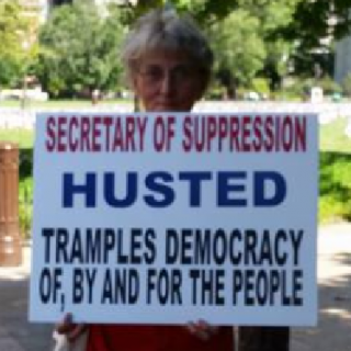 Woman holding sign against Jon Husted