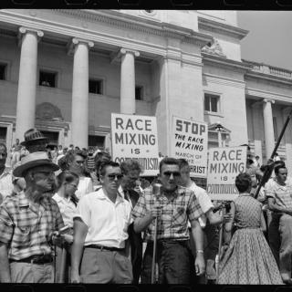 Black and white photo of protest in streets from 50s with sign saying something about race mixing