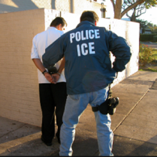 Back of man in blue jacket with white letters reading ICE putting another man with his back to us in handcuffs