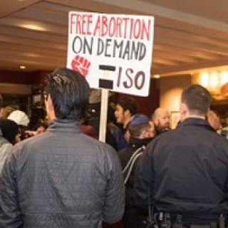 Backs of two men, one with a cop looking uniform on and the other with a sign that says Free Abortion on Deand ISO with a red fist