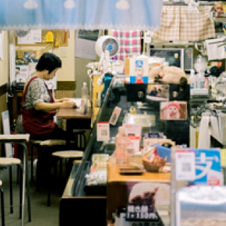 Person working at a desk in a shop filled with arts and crafts