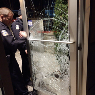 Shattered glass door and policemen