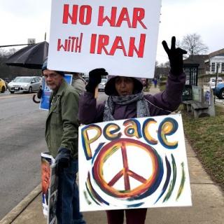 Woman holding No War with Iran and Peace protest signs