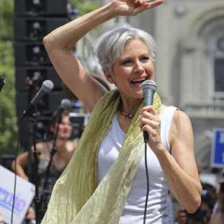 Jill Stein with her arm above her head and in a white tank top and yellow scarf outside at rally