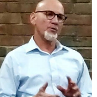 Bald white man with glasses with white goatee talking and making hand gestures
