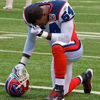 Football player wearing red white and blue football uniform kneeling on field