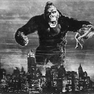 Big mean King Cong hovering over a city with a woman in his hand