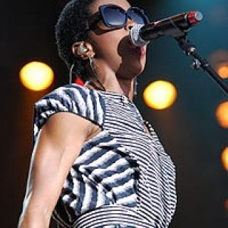 Black woman wearing sunglasses and a striped dress singing into a mic