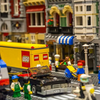 Storefronts made from legos and Lego word on side of truck and little lego people