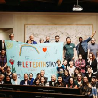 People posing with a sign saying Let Edith Stay