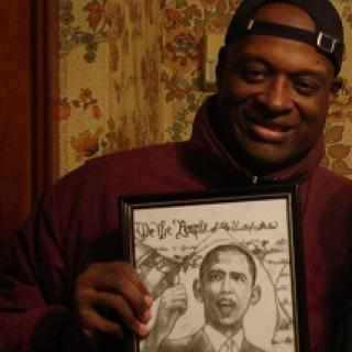Black man smiling and holding an illustration of Obama
