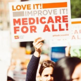 Woman holding up a sign saying Medicare For All! Love it! Improve it!
