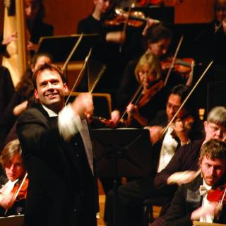 Man in front of orchestra conducting