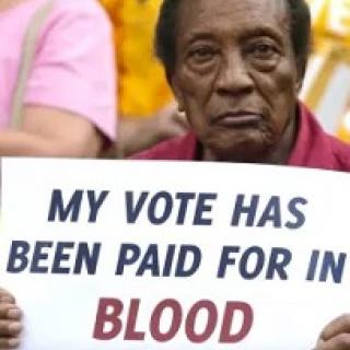 Black man holding a sign reading My vote has been paid for in BLOOD