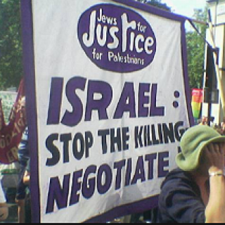 People protesting outside with sign saying Israel stop the killing, negotiate