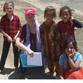 Older gray haired white woman posing outside with four dark skinned young girls