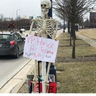 Skeleton leaning against a pole outside holding an anti-Pence sign