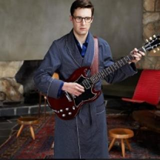 Young geeky guy with big black rimmed glasses wearing a bathrobe holding an electric guitar in a room with two wooden stools