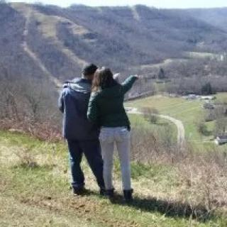 Backs of two people standing outside on a hill pointing off to the distance down in a valley