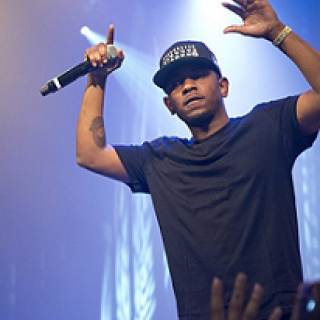 Black male rapper on stage with arms in air holding a mic