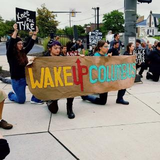 Young white people holding a sign saying Wake Up Columbus kneeling on ground and as part of a rally with lots of people behind them one with a sign saying Knee for Tyre