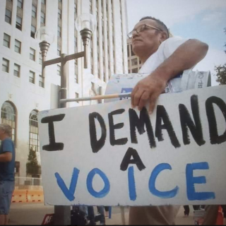 Man holding sign saying I Demand A Voice