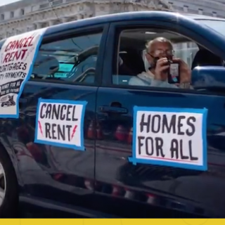Person in car in caravan with sign Homes for All