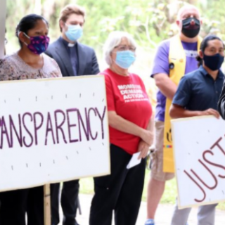People with signs saying Transparency and Justice