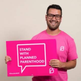 Man holding a sign saying Stand with Planned Parenthood