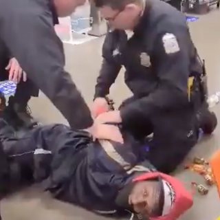 Cops holding a black man down