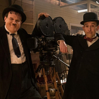 One large and one small man both in black suits with white shirts and hats leaning on an old time film projector