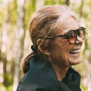 Older woman with big sunglasses facing right in a ponytail, smiling